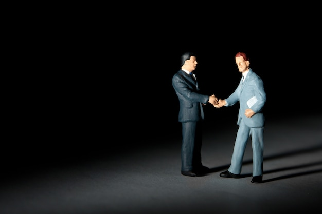 Miniaturfiguren von zwei erfolgreichen geschäftsleuten zum händeschütteln