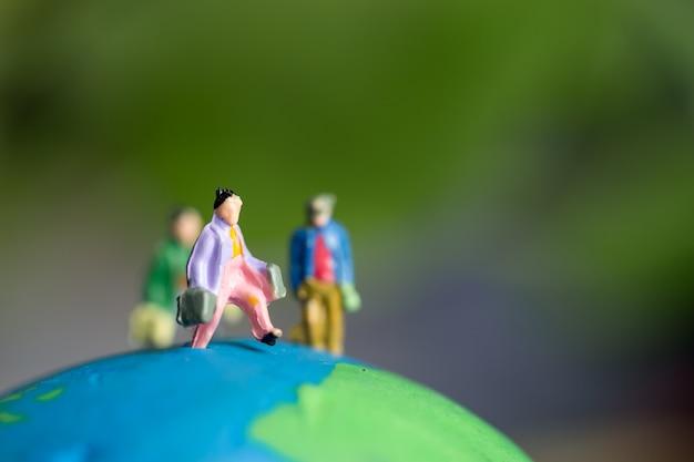 Miniaturfigurengruppe des jungen reisenden, der für reiseleute in reisen ins ausland reist, die auf grünem modell der erdkugel stehen
