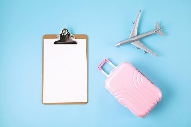Miniaturflugzeug und koffer über blauer wand. reisevorbereitung, tourismus, fluggesellschaften, billigflüge, gepäckverpackungskonzept. draufsicht, flach liegen.