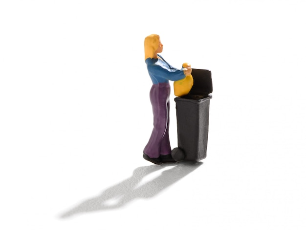 Miniaturfrau, die den hausmüll wegwirft