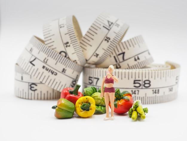 Miniaturfrau mit gemüse und messendem band auf weißem hintergrund, gesunder lebensstil