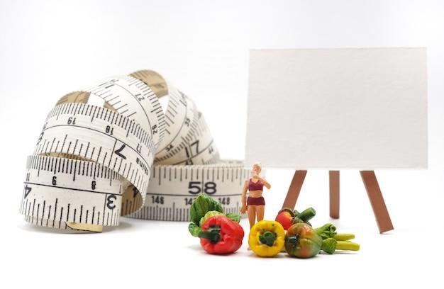 Miniaturfrau mit gemüse und messendem band