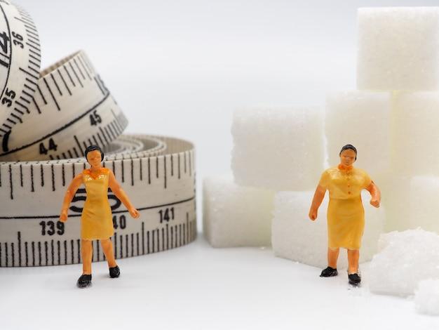 Miniaturfrau mit zucker und messendem band auf weißem hintergrund, gesunder lebensstil conc