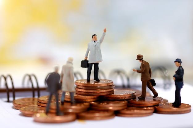 Miniaturgeschäftsleute, die auf schritt des münzengeldes stehen.