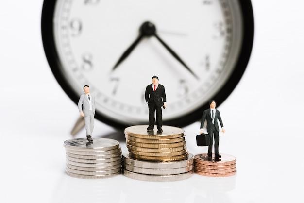 Miniaturgeschäftsleute stehen auf silbermünzen mit weckerhintergrund, zeit ist geldkonzept