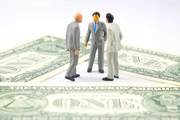 Miniaturgeschäftsleute stehen über einem dollarschein