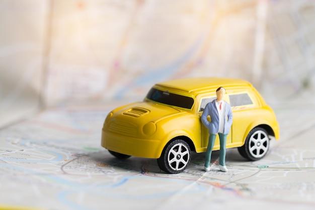 Miniaturgeschäftsleute und gelbes auto auf bangkok-stadtplan