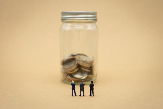 Miniaturgeschäftsmänner mit 3 leuten, die mit der rückseite verhandelt im geschäft stehen.