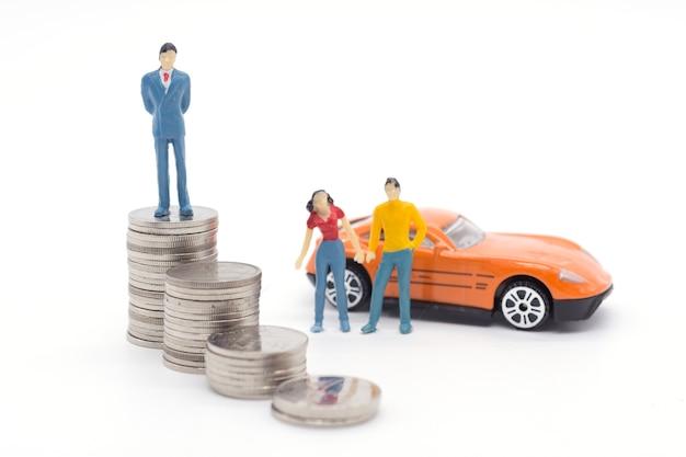 Miniaturgeschäftsmann, der auf münzen und dem auto hinten steht. spar- und darlehenskonzept.