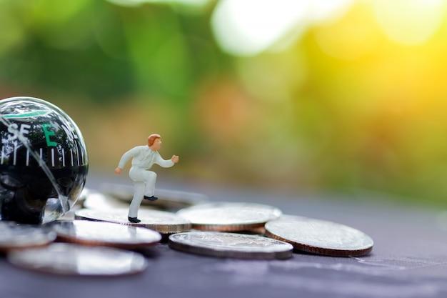 Miniaturgeschäftsmann, der auf münzenstapel und -kompaß läuft