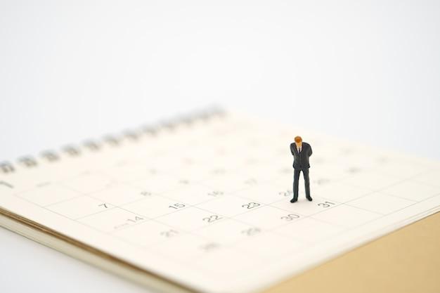 Miniaturgeschäftsmann, der auf weißem kalender steht