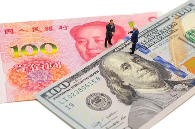 Miniaturgeschäftsmann mit banknote des us-dollars und chinas yuan auf gesellschaftssitzung