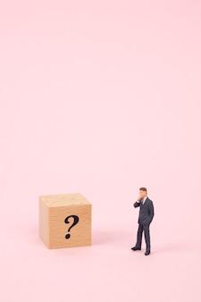 Miniaturgeschäftsmann mit fragezeichen auf hölzernem würfel