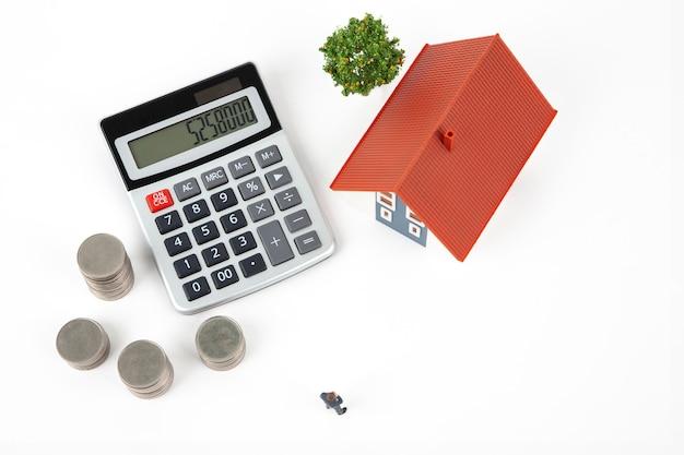 Miniaturgeschäftsmann und münzen mit musterhaus