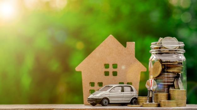 Miniaturgeschäftsmannfigur, die auf goldene münzen und ein automodell steht