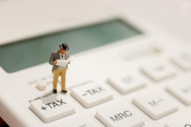 Miniaturgeschäftsmannstandlesung auf steuerknopf des taschenrechners.