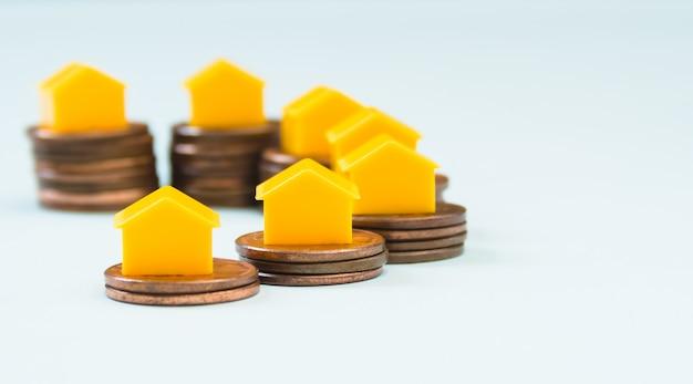Miniaturhaus auf 1-cent-münzenstapeln, immobilien und finanzkonzept
