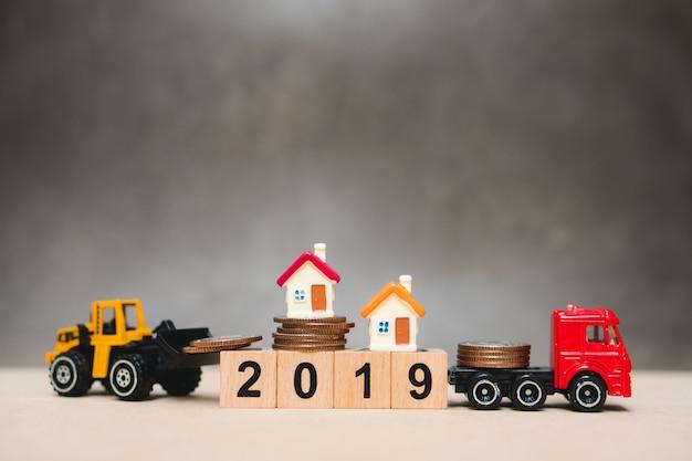 Miniaturhaus auf holzblock des jahres 2019 mit baufahrzeug