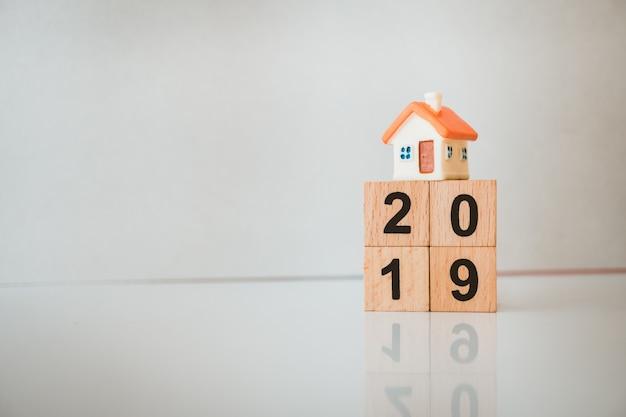 Miniaturhaus auf holzblockjahr 2019 unter verwendung als familien- und eigenschaftskonzept