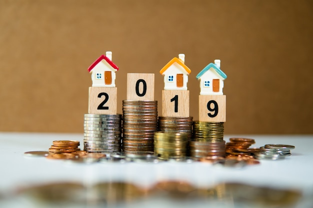 Miniaturhaus auf holzklotzjahr 2019 mit stapelmünzen