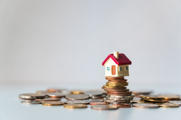 Miniaturhaus auf stapel von münzen unter verwendung als eigentum