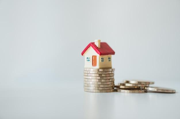 Miniaturhaus auf stapelmünzen auf grauem hintergrund unter verwendung als eigentum und geschäftskonzept