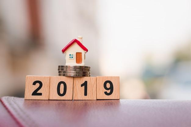 Miniaturhaus auf stapelmünzen und holzblockjahr 2019 unter verwendung als geschäfts- und eigentumskonzept
