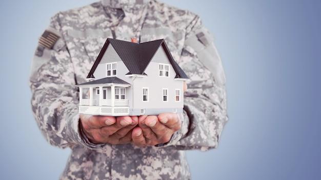 Miniaturhaus in soldatenhänden, helden, haus unter schutz.