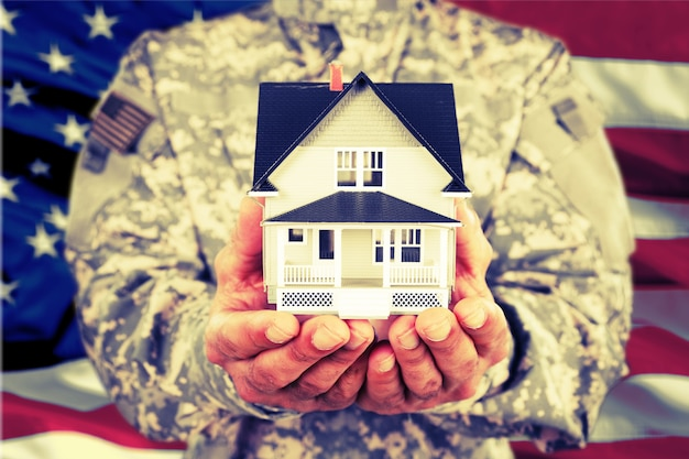 Miniaturhaus in soldatenhänden