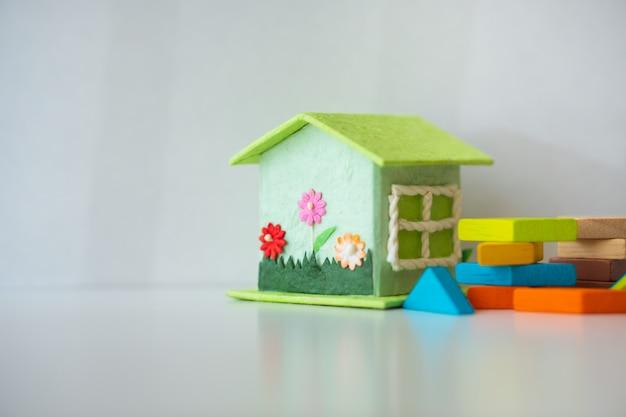 Miniaturhaus mit tangrampuzzlespiel auf weißem hintergrund