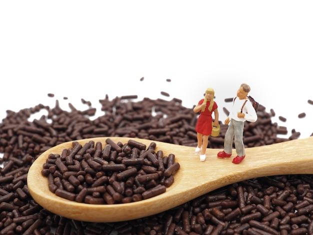 Miniaturjugendliche auf schokolade besprüht auf weißem hintergrund. diät-, fett- und gewichtsverlustkonzept.