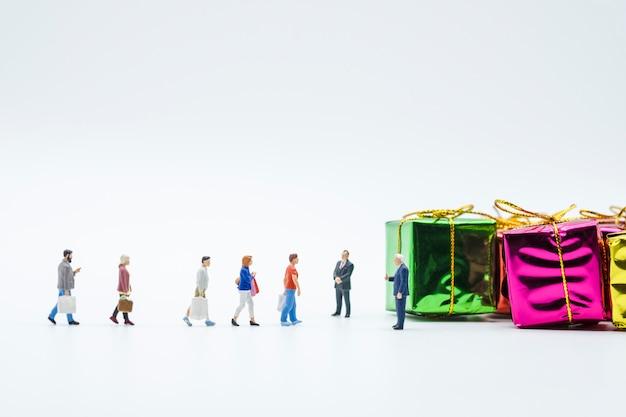 Miniaturkäufer: mann- und frauenhand tragen einkaufstasche und gehen auf weißen hintergrund