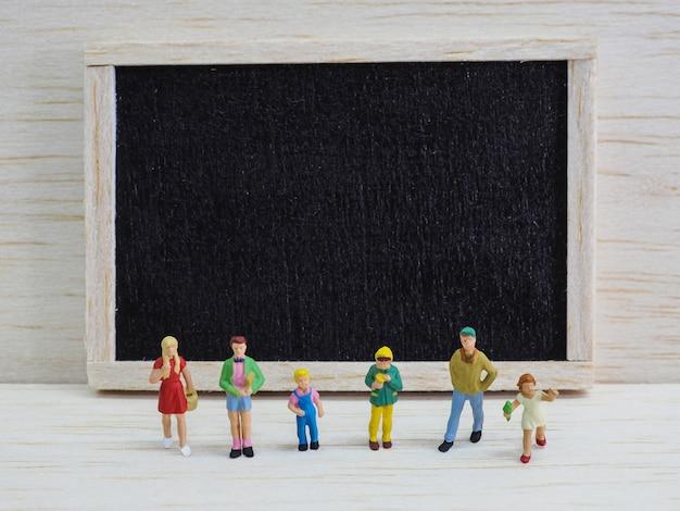Miniaturkinder, die vor einer tafel auf hölzernem hintergrund stehen. zurück zum schulkonzept.