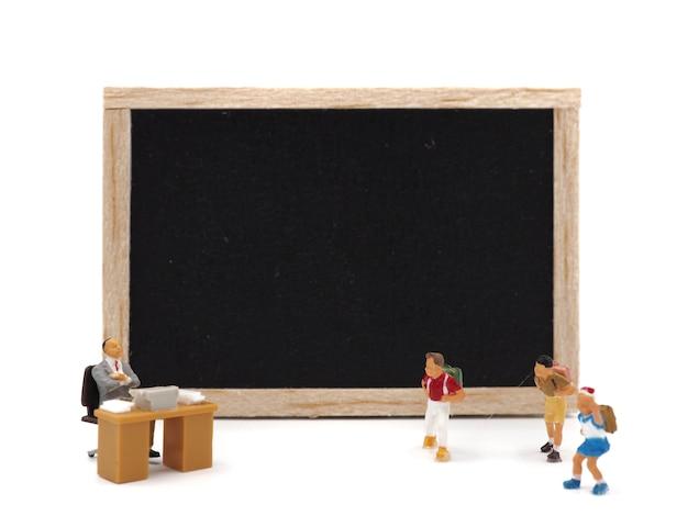 Miniaturkinder, die vor einer tafel auf weißem hintergrund stehen. zurück zum schulkonzept.
