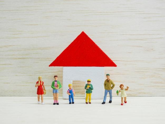 Miniaturkinder, die vor kleinem haus auf hölzernem hintergrund stehen. zurück zum schulkonzept.