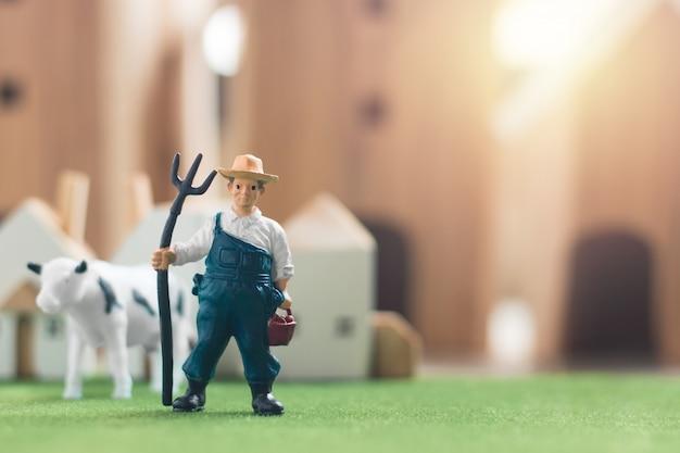 Miniaturlandwirt und kuh stellen modell auf simulationsgras dar