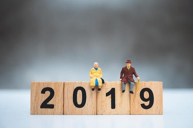 Miniaturleute, ältere leute, die auf hölzernem jahr 2019 verwenden als jobruhestandskonzept sitzen