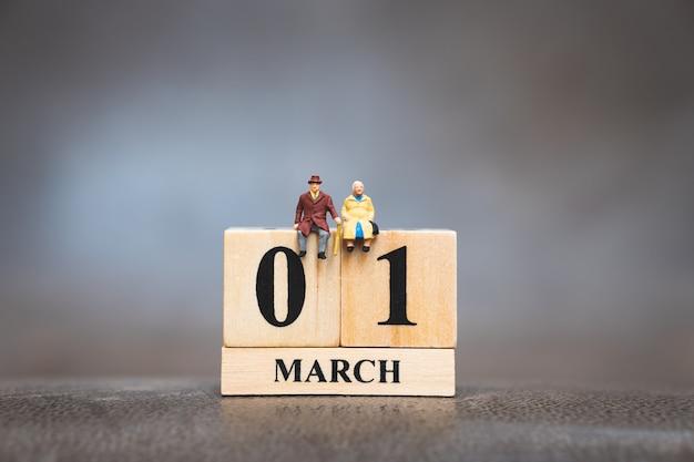 Miniaturleute, älterer mann und frau, die auf hölzernem kalender sitzen