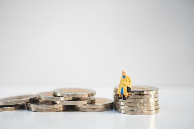 Miniaturleute, alte frau, die auf stapelmünzen als job-ruhestand und versicherung c sitzt