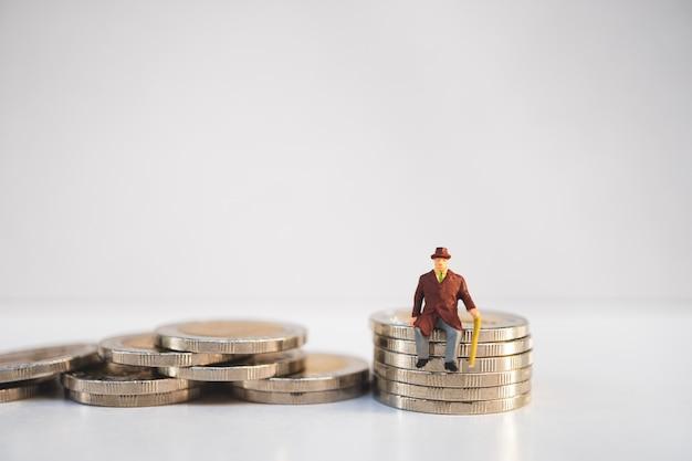 Miniaturleute, alter mann, der auf stapelmünzen als job-ruhestand und versicherungsbetrug sitzt