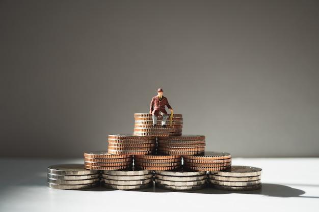 Miniaturleute, alter mann, der auf stapelmünzen als job-ruhestand und versicherungskonzept sitzt