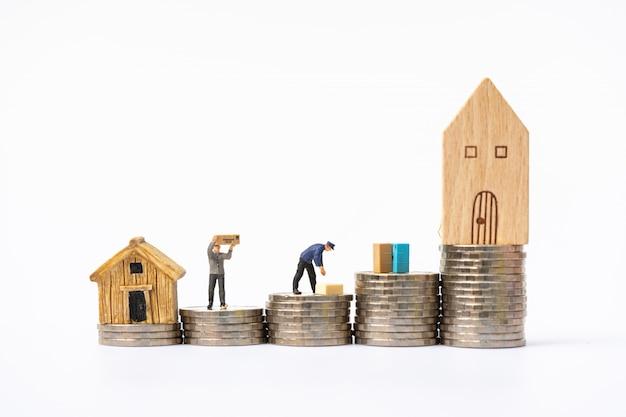 Miniaturleute, arbeiter, die sachen auf münzenstapeln in ein neues haus umziehen.