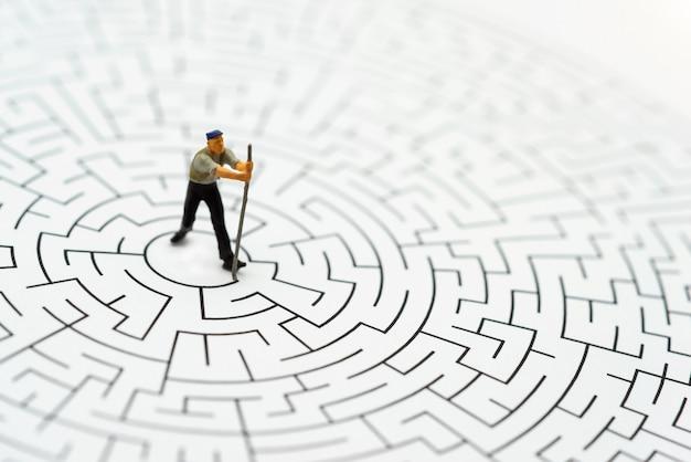 Miniaturleute, arbeitskraftmann, der die wände im labyrinth niederbricht