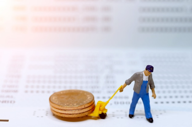 Miniaturleute: arbeitskraftmünzen stapeln auf buchbank.