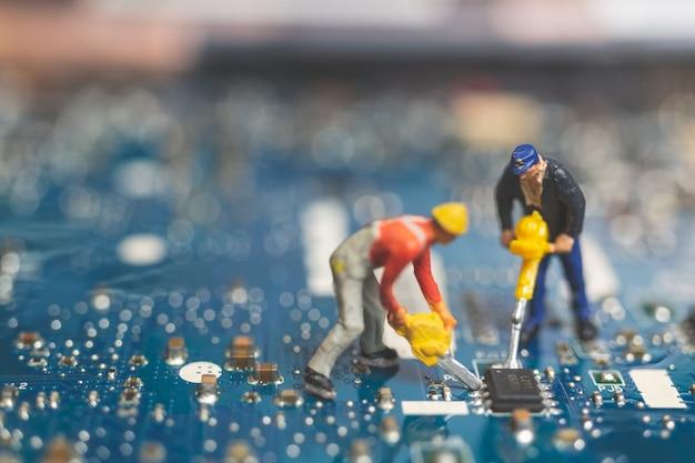Miniaturleute: arbeitskraftteam von den ingenieuren, die tastaturcomputerlaptop reparieren