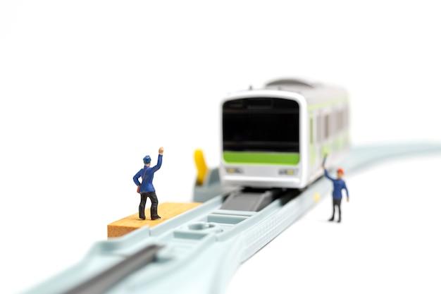 Miniaturleute: bahnpersonal arbeitet an der eisenbahn auf weißem hintergrund
