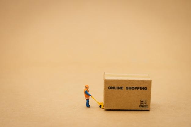 Miniaturleute bauarbeiter online-shopping mit einem einkaufswagen