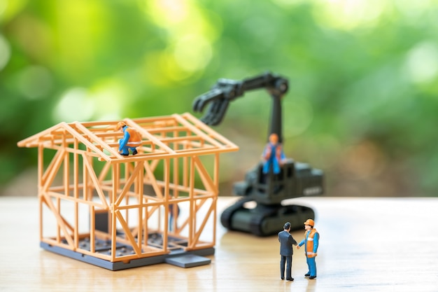 Miniaturleute bauarbeiterreparatur ein musterhausmodell
