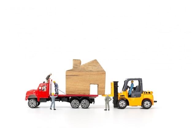 Miniaturleute: bewegliches haus des arbeitskraftteams, immobilien und eigentumsgeschäftskonzept