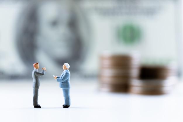Miniaturleute, der geschäftsmann, der auf dollarschein mit münzenstapel steht, steigern hintergrund.